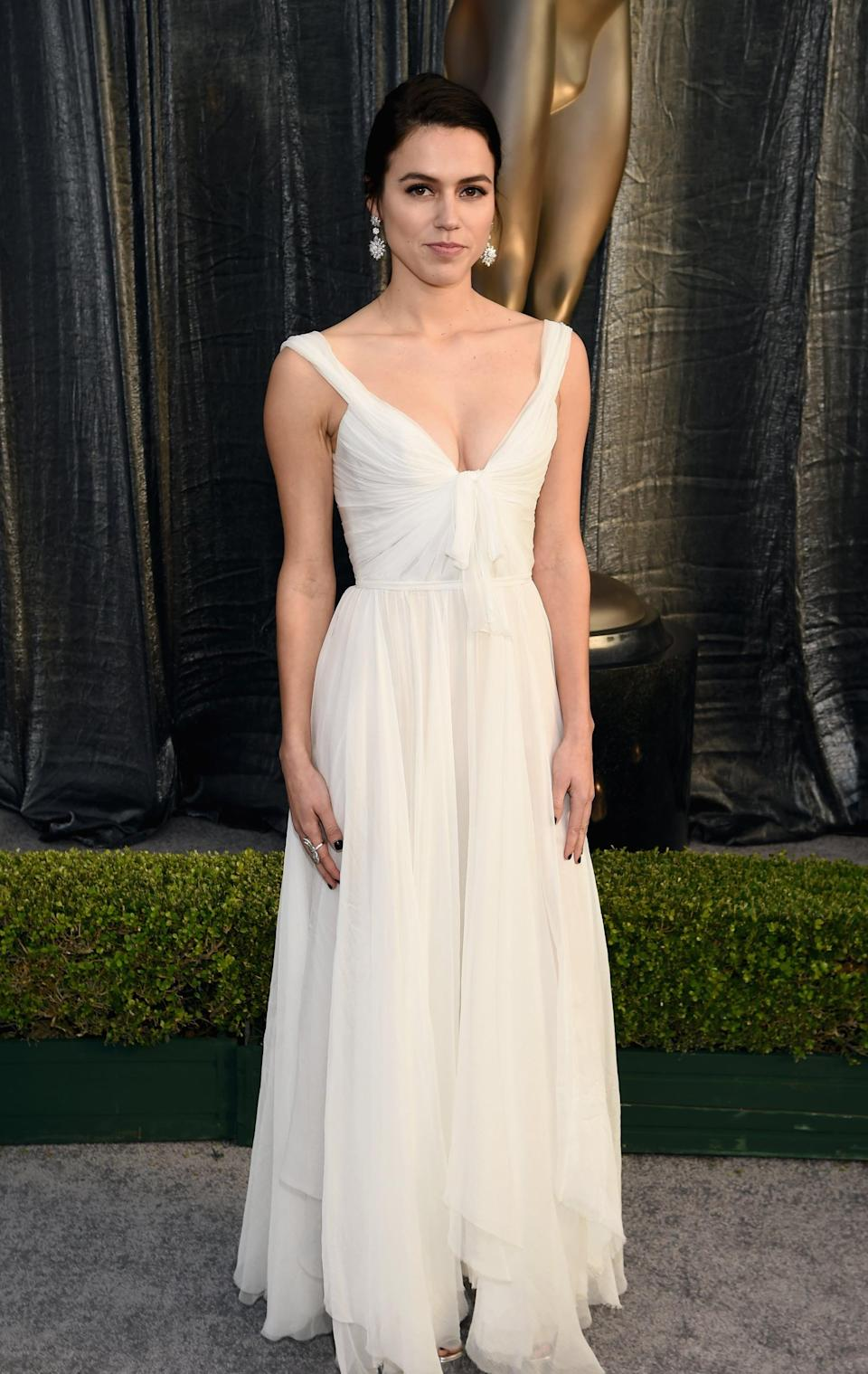 <p>Wearing a white Paolo Sebastian gown with dangling earrings.</p>