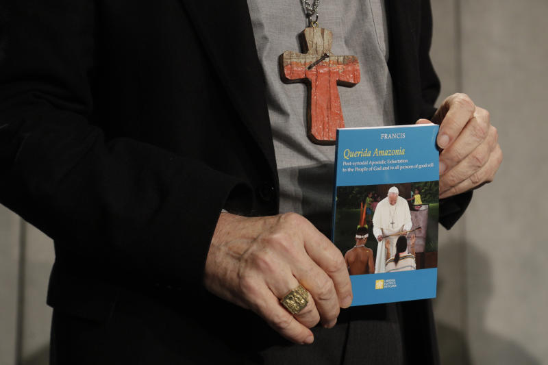 """Cardinal Michael Czerny holds a copy of the post-synodal apostolic exhortation """"Querida Amazonia"""" written by Pope Francis during a press conference at the Vatican, Wednesday, Feb. 12, 2020. (AP Photo/Gregorio Borgia)"""