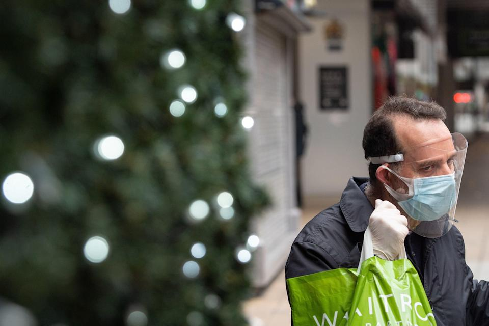 <p>A man wears a face covering while on Oxford Street</p> (PA)