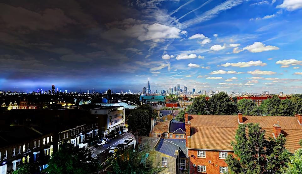 Two images of central London from a rooftop merged together to show the transition from night to day in a single image.