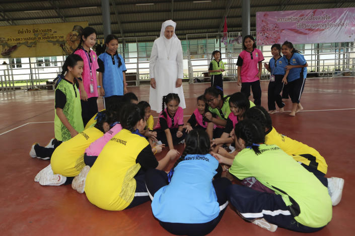In this Aug. 27, 2019, photo, ST. Mary's School Vice Principal Sister Ana Rosa Sivori, rear center, watches students play during a lunch break at the girls' school in Udon Thani, about 570 kilometers (355 miles) northeast of Bangkok, Thailand. Sister Ana Rosa Sivori, originally from Buenos Aires in Argentina, shares a great-grandfather with Jorge Mario Bergoglio, who, six years ago, became Pope Francis. So, she and the pontiff are second cousins. (AP Photo/Sakchai Lalit)