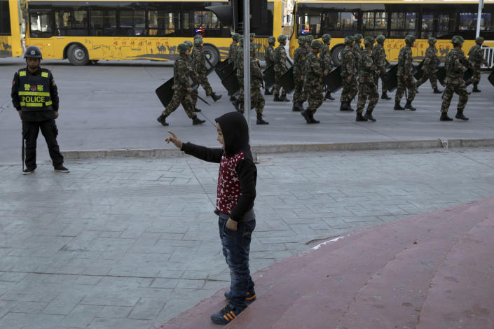 FILE - In this Nov. 5, 2017, file photo, a child reacts as security personnel march by in a show of force in Kashgar in western China's Xinjiang region. A Chinese Communist Party official signaled Monday, Dec. 21, 2020 that there would likely be no let-up in its crackdown in the Xinjiang region, but said the government's focus is shifting more to addressing the roots of extremism. (AP Photo/Ng Han Guan, File)