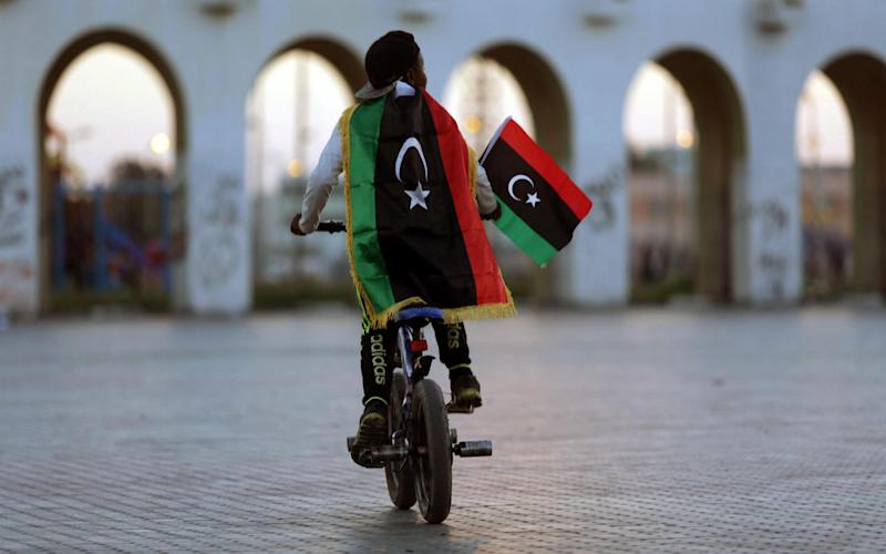 A boy wearing a Libyan flag takes part in a celebration marking the sixth anniversary of the Libyan revolution - AFP