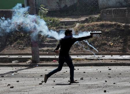 A demonstrator fires a homemade mortar towards riot police during a protest, in Managua