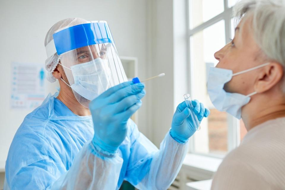 doctor in face shield and ppe giving older woman covid test