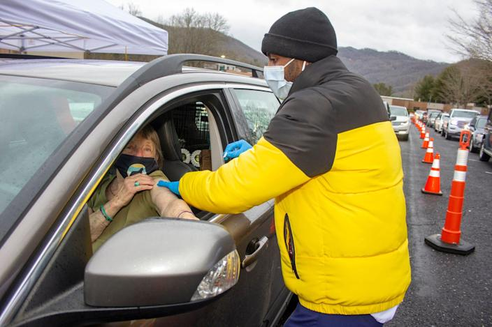 Mars Hill University senior nursing major Reggie Wright of Greenville, S.C., prepares to administer a COVID-19 vaccine during a drive-in clinic at Mountain Heritage High School in Burnsville on Monday.