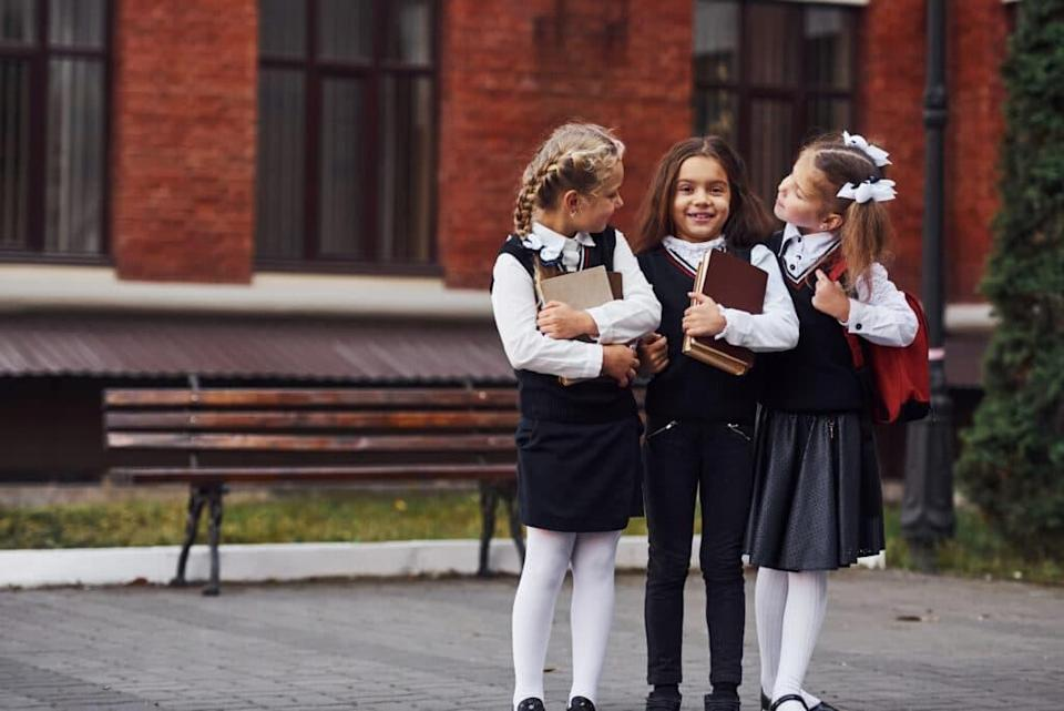 Group of female kids in school uniform that is outdoors together near education building