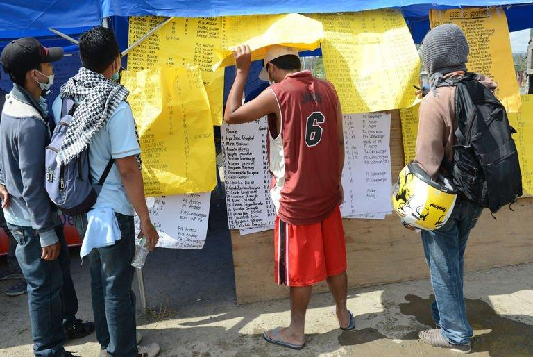 Residents look at the lists of missing relatives displayed near the municipal hall in New Bataan, Compostela province on December 12, 2012 nearly one week after the southern part of the Philippines was hit by Typhoon Bopha. The death toll from the strongest typhoon to hit the Philippines this year has climbed above 900, with hundreds still missing, the government said