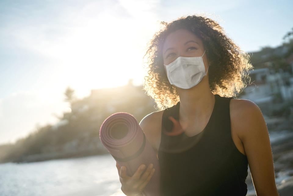 A young woman wearing a face mask outdoors while holding a yoga mat.