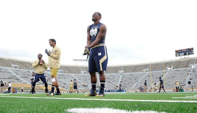 Players loosen up on the new turf prior to an NCAA college football game between Notre Dame and Rice in South Bend, Ind. Saturday Aug. 30, 2014. (AP Photo/Joe Raymond)
