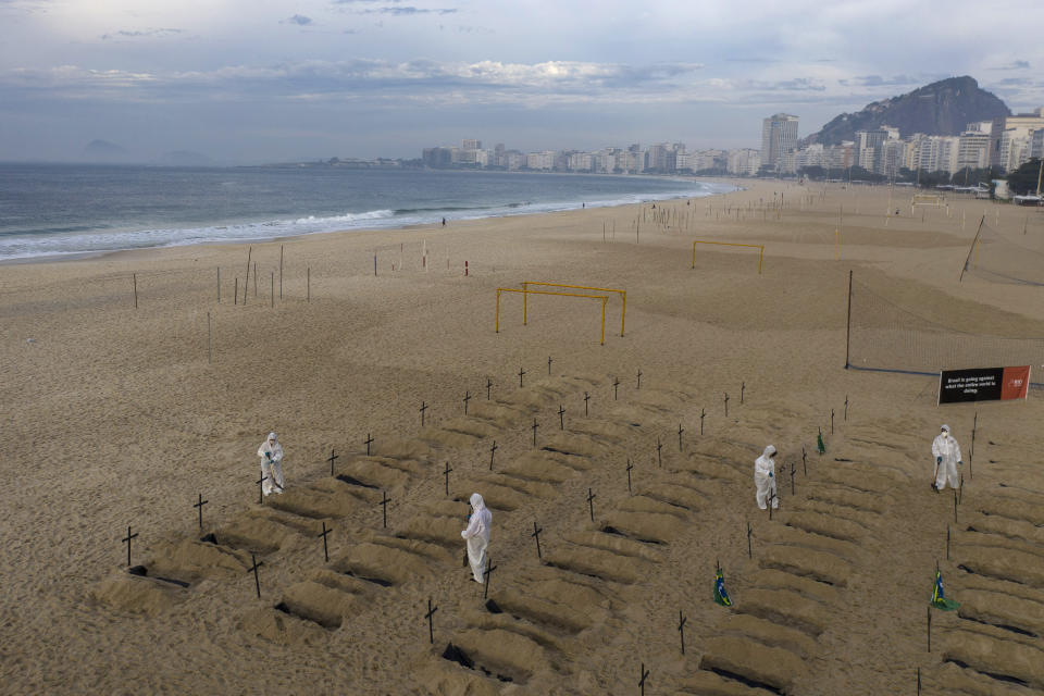 Activists in costume dig symbolic graves on Copacabana beach as a protest, organized by the NGO Rio de Paz, against the government's handling of the COVID-19 pandemic in Rio de Janeiro, Brazil, Thursday, June 11, 2020. (AP Photo/Leo Correa)