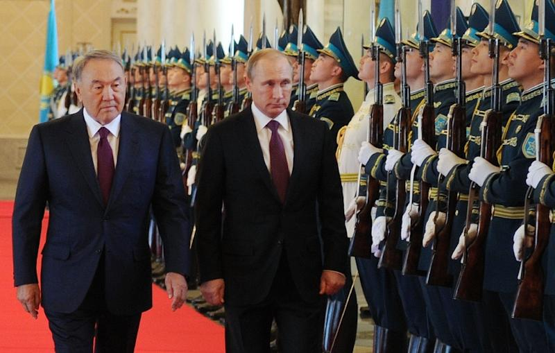 Kazakh President Nursultan Nazarbayev (L) and Russian President Vladimir Putin review an honor guard during a ceremony in Astana, on October 15, 2015 (AFP Photo/Ilyas Omarov)
