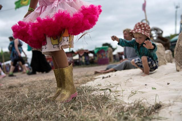 <p>A young girl wearing wellington boots plays with sand with a young boy at Glastonbury Festival Site on Worthy Farm in Pilton on June 23, 2017 near Glastonbury, England. (Photo: Chris J Ratcliffe/Getty Images) </p>