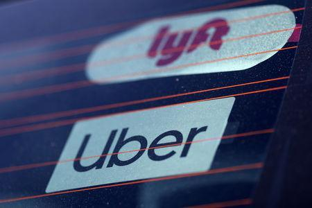 FILE PHOTO: Uber and Lyft signs on a car in Redondo Beach, California, U.S., March 25, 2019. REUTERS/Lucy Nicholson -/File Photo