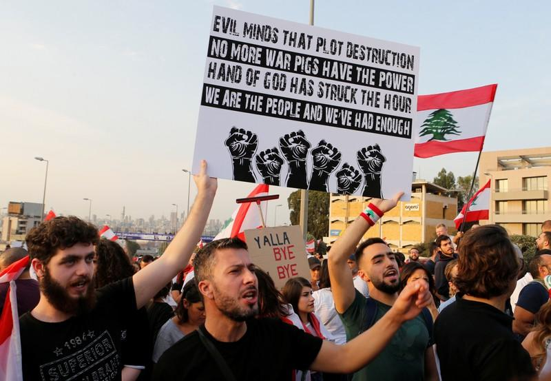 Demonstrators hold banners and chant slogans during ongoing anti-government protests in Hazmiyeh