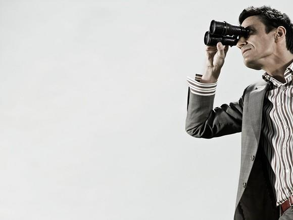 Man in a blazer looking through binoculars.