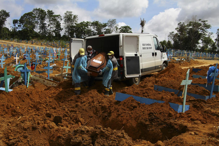 Cemetery workers carry the remains of 89-year-old Abilio Ribeiro, who died of the new coronavirus, to bury at the Nossa Senhora Aparecida cemetery in Manaus, Amazonas state, Brazil, Wednesday, Jan. 6, 2021. Manaus declared on Jan. 5 a 180-day state of emergency due to a surge of new cases of coronavirus. (AP Photo/Edmar Barros)
