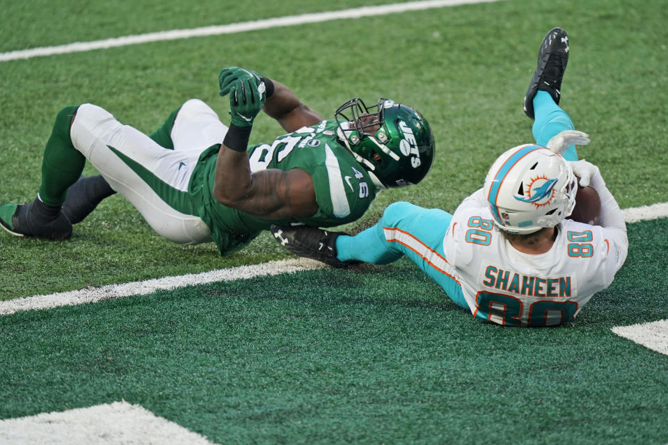 Miami Dolphins' Adam Shaheen, right, catches a touchdown pass in front of New York Jets' Neville Hewitt during the second half of an NFL football game, Sunday, Nov. 29, 2020, in East Rutherford, N.J. (AP Photo/Corey Sipkin)