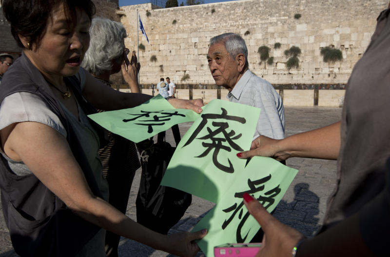 A Japanese group of survivors of the Atomic atack on Hiroshima hold signs calling for the abolition of Nuclear weapons at the Western Wall,  the holiest site where Jews can pray in Jerusalem's old city, Monday, Sept. 10, 2012. A group of survivors from the Hiroshima atomic bomb attack have held a protest in Jerusalem calling for the end of nuclear weapons. In 1945, the United States dropped an atomic bomb on the city of Hiroshima, leading to Japan's surrender and the end of World War II. The blast destroyed most of the city and killed as many as 140,000 people. (AP Photo/Sebastian Scheiner)