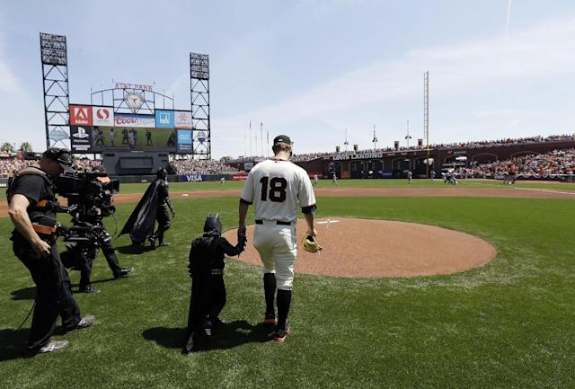 Miles Scott, second from right, dressed as Batkid, walks to the mound with San Francisco Giants pitcher Matt Cain (18) to throw the ceremonial first pitch before a home opener baseball game between the Giants and the Arizona Diamondbacks in San Francisco, Tuesday, April 8, 2014. On Nov. 15, 2013, Scott, a Northern California boy with leukemia, fought villains and rescued a damsel in distress as a caped crusader through The Greater Bay Area Make-A-Wish Foundation. (AP Photo/Eric Risberg, Pool)