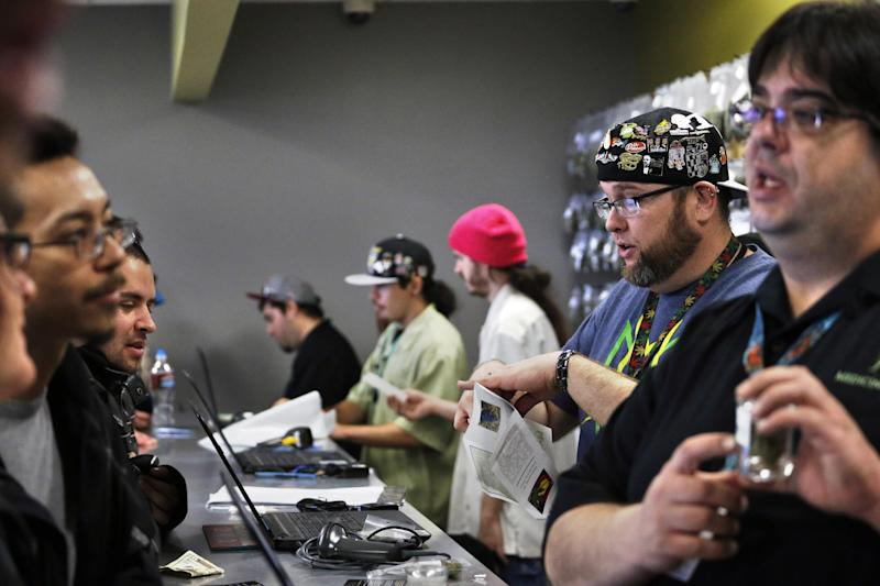 "Employees help customers at the crowded sales counter inside Medicine Man marijuana retail store, which opened as a legal recreational retail outlet in Denver on Wednesday, Jan. 1, 2014. Colorado began retail marijuana sales on Jan. 1, a day some are calling ""Green Wednesday."" (AP Photo/Brennan Linsley)"