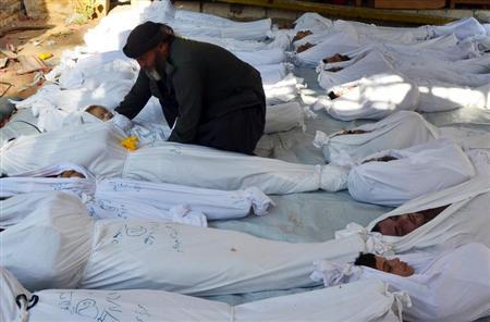 A man holds the body of a dead child among bodies of people activists say were killed by nerve gas in the Ghouta region, in the Duma neighbourhood of Damascus