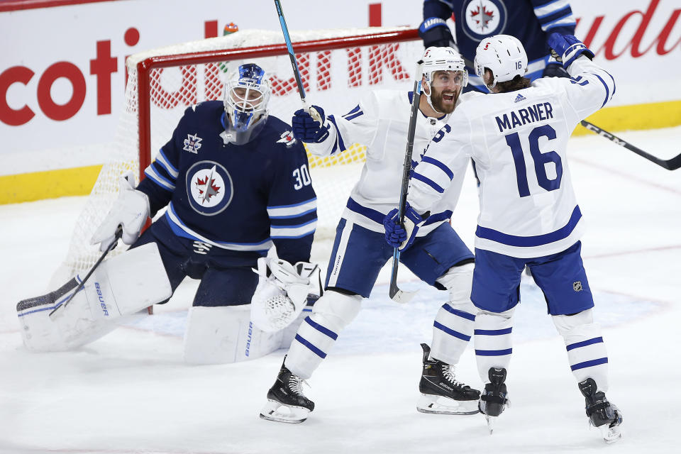 Toronto Maple Leafs' Nick Foligno (71) and Mitchell Marner (16) celebrate Marner's goal on Winnipeg Jets goaltender Laurent Brossoit (30) during the second period of an NHL hockey game Thursday, April 22, 2021, in Winnipeg, Manitoba. (John Woods/The Canadian Press via AP)