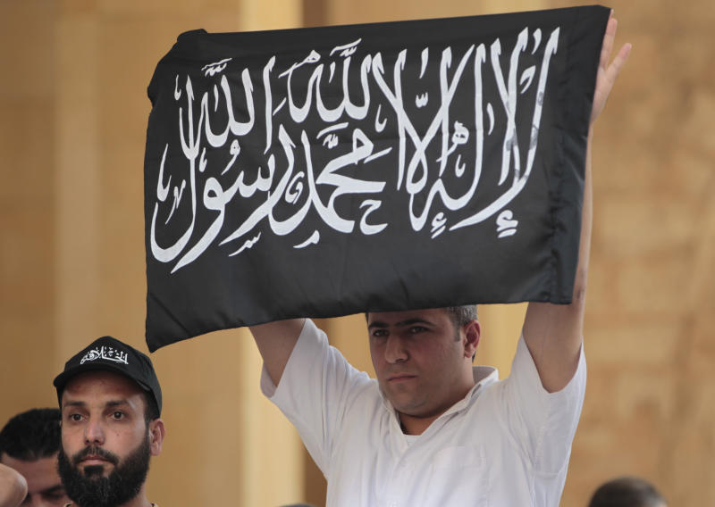"""A man holding the flag of an Islamic group, reading in Arabic: """"There is no God only the God, and Mohammed is his prophet"""" protests against the Syrian regime inside a mosque, in downtown Beirut, Lebanon, Friday June 3, 2011. Syrian troops pounded a central town with artillery and heavy machine gun fire Friday, killing at least two people in the latest onslaught  as authorities cut off Internet service in several regions in an apparent move to prevent the uploading of videos of anti-regime demonstrations,  activists said. (AP Photo/Hussein Malla)"""