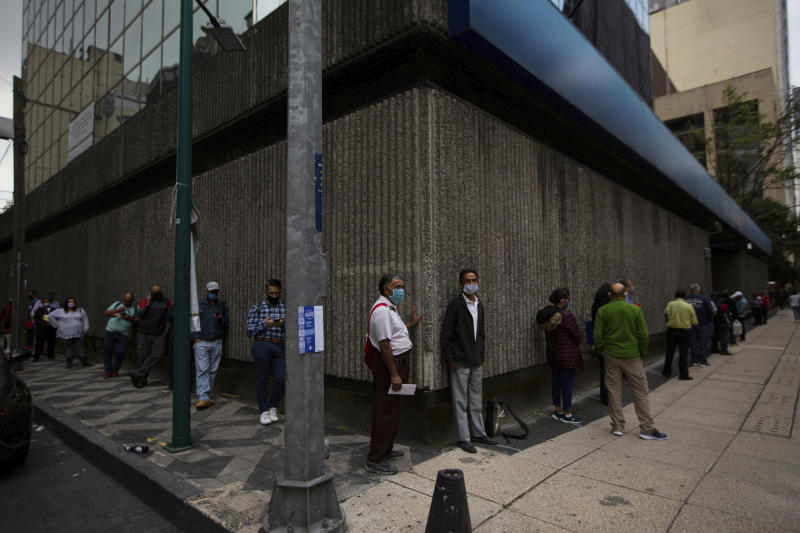 Bank customers stand at a distance, as a measure to avoid the spread of the new coronavirus, as they line up outside a bank in Mexico City, Monday, June 29, 2020. Mexico City is expected to move to the next stage of its gradual reopening this week. (AP Photo/Fernando Llano)