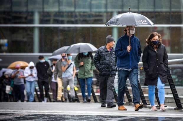 People are pictured in line for their COVID-19 vaccination at Canada Place in Vancouver, British Columbia on Thursday May 27, 2021. (Ben Nelms/CBC - image credit)