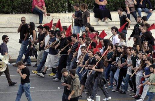 <p>Young demonstrators march in front of the Greek parliament in central Athens during protests against new austerity measures and a rally marking a 48-hour general strike, on November 6. Greek lawmakers vote Wednesday on austerity measures needed to unlock international aid and stave off bankruptcy despite strikes and public anger against billions more euros in tax hikes and pension cuts</p>