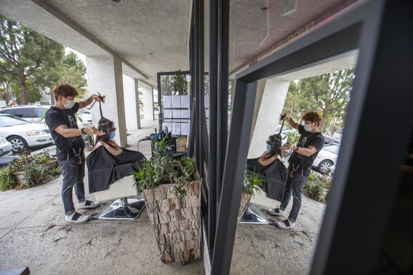 "Travis Vu cuts a client's hair in one of two socially-distanced chairs in front of his salon in Fountain Valley. He said he could never have imagined moving his operations outside, but is doing his best to keep business afloat and four employees working. <span class=""copyright"">(Allen J. Schaben / Los Angeles Times)</span>"