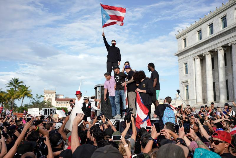 Puerto Rican singer Ricky Martin (C), Puerto Rican rapper Rene Perez, aka Residente, (R) Puerto Rican reggaeton singer Bad Bunny (top), take part of a demonstration demanding Governor Ricardo Rossello's resignation in San Juan, Puerto Rico on July 17, 2019. (Photo: Eric Rojas/AFP/Getty Images)