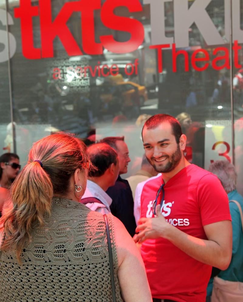 This June 19, 2013 photo shows Michael Buffer, TKTS patron services manager, talking to a customer at the Times Square discount ticket booth in New York. The booth turns 40 this summer and hires young people to help tourists and New Yorkers alike make decisions about shows they want to see. (AP Photo/Mark Kennedy)