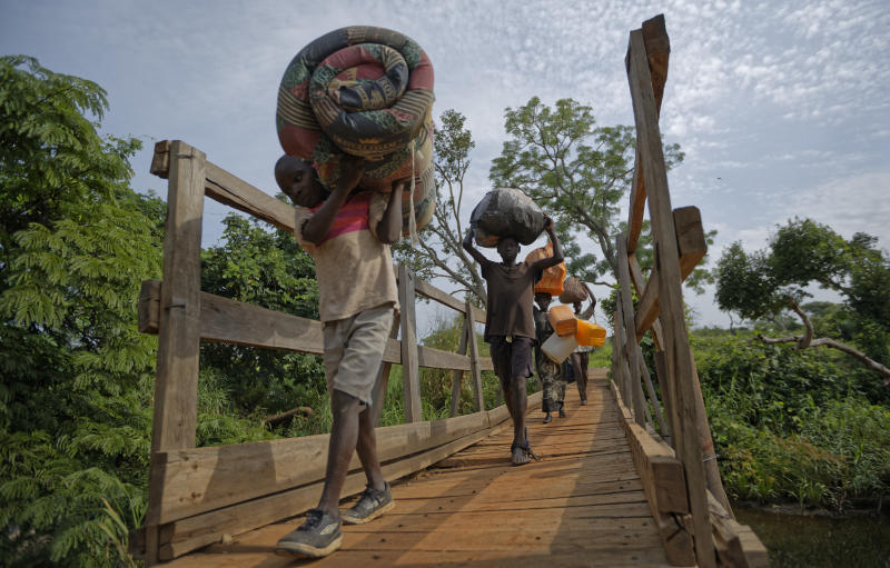"FILE - In this Thursday, June 8, 2017 file photo, from left to right, South Sudanese refugees Thomas Wani, 12, brother Peter Lemi, 14, mother Rose Sunday, and father Julius Lezu, cross a wooden bridge from South Sudan to Uganda at the Busia crossing, near Kuluba, in northern Uganda. The latest report on human rights abuses in South Sudan's five-year civil war, released by a United Nations commission Friday, Feb. 23, 2018 says it has identified more than 40 senior military officials ""who may bear individual responsibility for war crimes."" (AP Photo/Ben Curtis, File)"