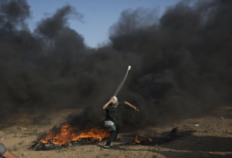 A Palestinian protester hurls stones at Israeli troops during a protest at the Gaza Strip's border with Israel, Friday, Sept.28, 2018. (AP Photo/Khalil Hamra)