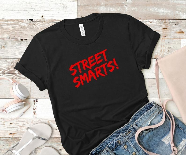 """<p>Give your friends a lesson in stranger danger from Detective J. J. Bittenbinder with this <a href=""""https://www.popsugar.com/buy/Street-Smarts-T-Shirt-509118?p_name=%22Street%20Smarts%21%22%20T-Shirt&retailer=etsy.com&pid=509118&price=23&evar1=pop%3Auk&evar9=46829575&evar98=https%3A%2F%2Fwww.popsugar.com%2Fcelebrity%2Fphoto-gallery%2F46829575%2Fimage%2F46829940%2FStreet-Smarts-T-Shirt&list1=gifts%2Chumor%2Cgift%20guide%2Cjohn%20mulaney%2Centertainment%20gifts&prop13=api&pdata=1"""" rel=""""nofollow"""" data-shoppable-link=""""1"""" target=""""_blank"""" class=""""ga-track"""" data-ga-category=""""Related"""" data-ga-label=""""https://www.etsy.com/listing/685058237/john-mulaney-street-smarts-quote-shirt?ga_order=most_relevant&amp;ga_search_type=all&amp;ga_view_type=gallery&amp;ga_search_query=john+mulaney&amp;ref=sr_gallery-1-3&amp;organic_search_click=1&amp;frs=1"""" data-ga-action=""""In-Line Links"""">""""Street Smarts!"""" T-Shirt</a> ($23).</p>"""