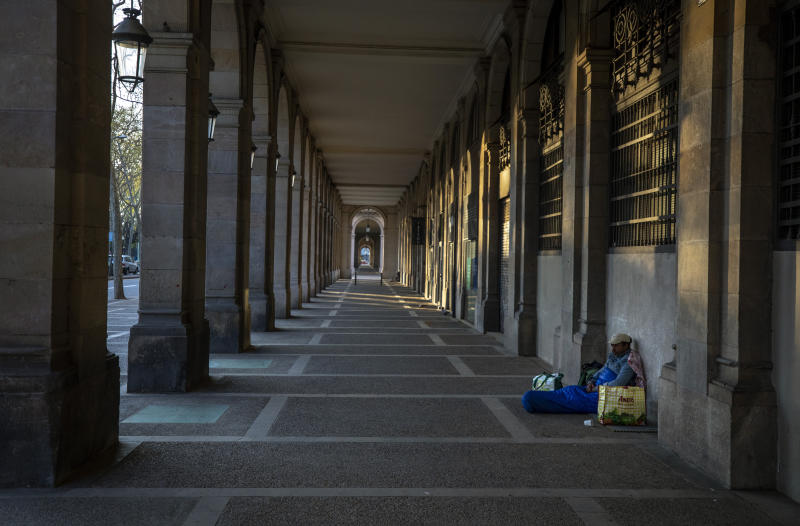 """In this Friday, March 20, 2020 photo, Riccardo, 32, sits in empty arcades in downtown Barcelona, Spain. """"I thought I had seen everything during all these years sleeping in the street, but no. This silence on the street all day scares me... more than the virus itself ..."""" says Riccardo, 32, who has been sleeping on the street for more than 10 years. (AP Photo/Emilio Morenatti)"""