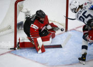 Alex Carpenter, right, of the United States, scores against Japan goalie Nana Fujimoto during first-period quarterfinal IIHF women's world championship hockey game action in Calgary, Alberta, Saturday, Aug. 28, 2021. (Jeff McIntosh/The Canadian Press via AP)