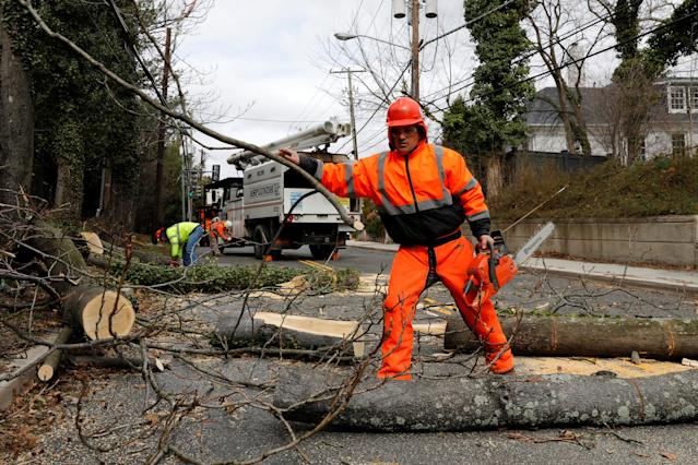 <p>A worker removes a fallen tree blocking a road on Foxholl Road as high-wind weather conditions continue in Washington, March 2, 2018. (Photo: Yuri Gripas/Reuters) </p>