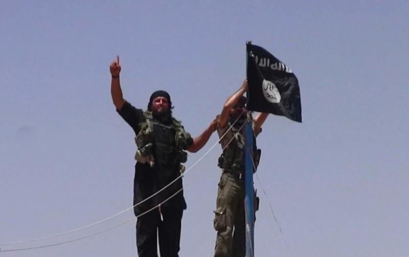 An image made available by jihadist Twitter account Al-Baraka news on June 11, 2014 allegedly shows Islamic State militants hanging their flag near the Syrian-Iraqi border (AFP Photo/)
