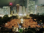 FILE - In this June 4, 1997, file photo, thousands of people attend a candlelight vigil at Hong Kong's Victoria Park, to mark the 8th anniversary of the military crackdown on a pro-democracy student movement in Beijing on the same day in 1989, as Hong Kong entered its last month as a British colony. (AP Photo/Franki Chan, File)