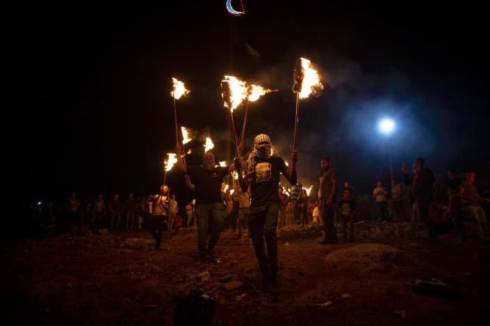 Palestinian demonstrators march with torches during a demonstration against the West Bank Jewish settlement outpost of Eviatar that was rapidly established last month, at the Palestinian village of Beita, near the West Bank city of Nablus, Sunday, June 27, 2021. The Palestinians say it was established on their farmland and fear it will grow and merge with other large settlements in the area. (AP Photo/Majdi Mohammed)