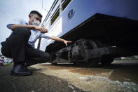 Yuta Azumi of the train planning division of Hiroshima Electric Railway Co., Ltd., explains a tram which survived the Hiroshima atomic bombing at a train maintenance facility in Hiroshima, western Japan, Monday, Aug. 3, 2020. It has been restored and repainted its original colors, will run on the street on Aug. 6 to commemorate the day of the U.S. first atomic bombing in the city. (AP Photo/Eugene Hoshiko)