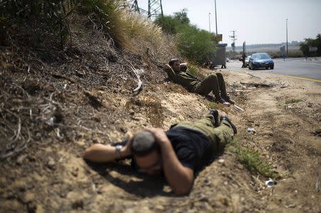 Israeli army reservists take cover as a siren sounds warning of incoming rockets near the southern city of Ashkelon July 23, 2014. REUTERS/Amir Cohen