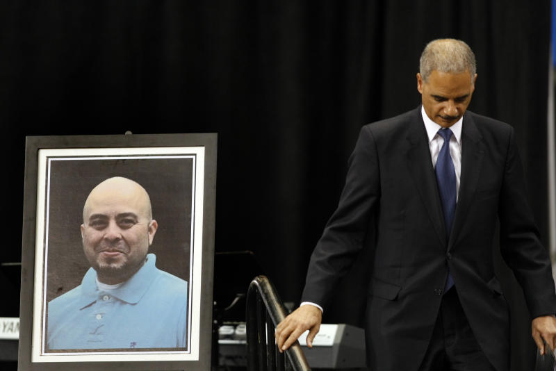 Attorney General Eric Holder walks past a portrait of slain TSA officer Gerardo Hernandez after delivering remarks during the public memorial service for Hernandez, Tuesday, Nov. 12, 2013. Hernandez was the first TSA officer killed in the line of duty when a gunman pulled a rifle from a bag and shot the 39-year-old father of two on Nov. 1, at Los Angeles International Airport. Two TSA officers and a teacher were injured before airport police wounded the gunman, Paul Ciancia. (AP Photo/ Los Angeles Times, Al Seib, Pool)
