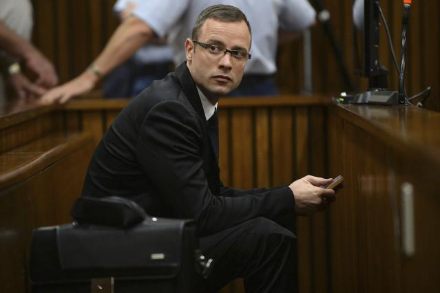 Olympic and Paralympic track star Oscar Pistorius sits in the dock during court proceedings at the North Gauteng High Court in Pretoria March 14, 2014. Pistorius is on trial for murdering his girlfriend Reeva Steenkamp at his suburban Pretoria home on Valentine's Day last year. REUTERS/Phill Magakoe/Pool (SOUTH AFRICA - Tags: SPORT ATHLETICS CRIME LAW)