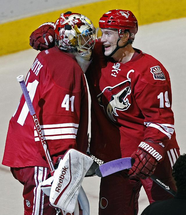 Phoenix Coyotes goalie Mike Smith (41), left, celebrates with Shane Doan (19) after scoring a third period goal during an NHL hockey game against the Detroit Red Wings on Saturday, Oct. 19, 2013, in Glendale, Ariz. (AP Photo/Rick Scuteri)