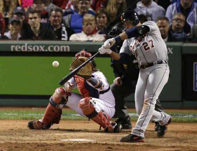 Detroit Tigers' Jhonny Peralta hits a double in front of Boston Red Sox catcher David Ross off Red Sox relief pitcher Craig Breslow in the eighth inning during Game 1 of the American League baseball championship series Saturday, Oct. 12, 2013, in Boston. (AP Photo/Charlie Riedel)