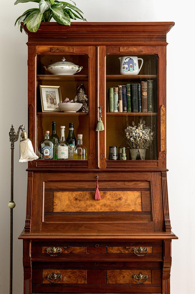 "Prior to finding this Eastlake secretary, the space held a bar cart, which was ""totally underutilized,"" Sean explains. They initially fell in love with a similar piece on 1stdibs, but it was way too expensive for their budget so they hunted around, and ultimately found this gem at a New Jersey antique market, and it's become one of their favorite pieces at home."